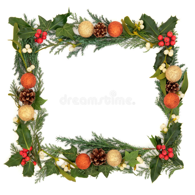 Christmas Border. Of holly, ivy, mistletoe with gold and orange bauble decorations over white background stock photos