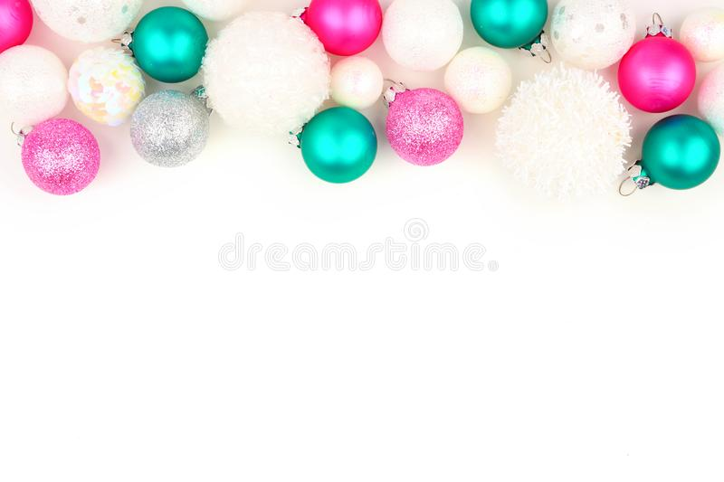 Christmas border of pastel and white ornaments over white. Christmas border of pastel pink, green and white ornaments on a white background stock photography