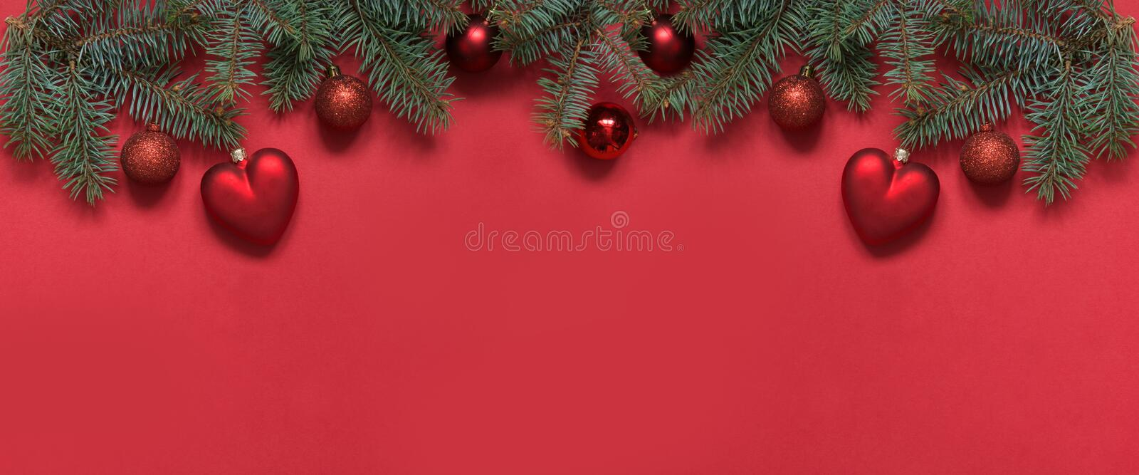 Christmas border of red balls and heart, evergreen branches on red. View from above, flat lay. Xmas. Template, greeting New Year. Christmas border of red balls stock images