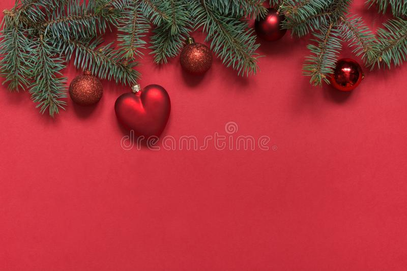 Christmas border of red balls and heart, evergreen branches on red. View from above, flat lay. Xmas holiday. Template, mockup,. Greeting New Year card stock photography