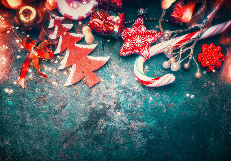 Christmas border with red decoration, christmas tree and candy on dark blue vintage background. Top view royalty free stock images