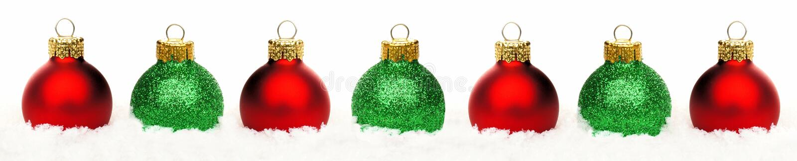 Christmas border of red and green baubles in snow isolated royalty free stock photos