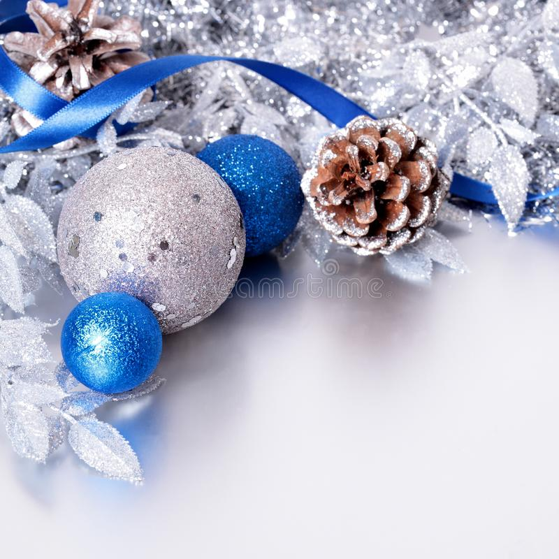 Christmas border with silver and blue balls on silver background. Christmas border with silver and blue decorations on silver reflection background square royalty free stock photo