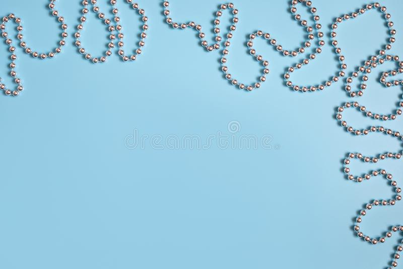 Christmas border with silver garland on pastel blue background. Space for text. Greeting card. Winter concept stock photos