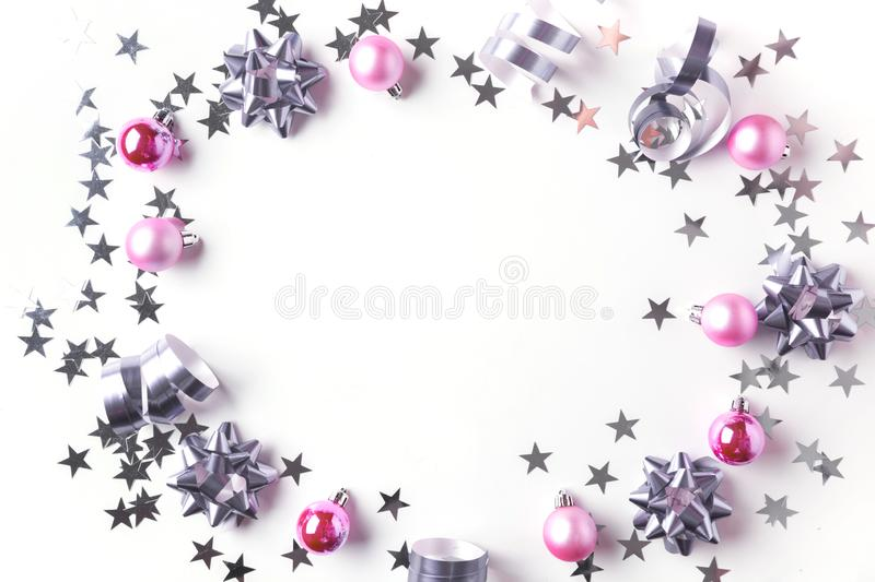 Christmas border of silver and pink pastel decoration, balls , tinsel, star, glitter on white. Xmas background. Flat lay style. Top view with copy space royalty free stock images