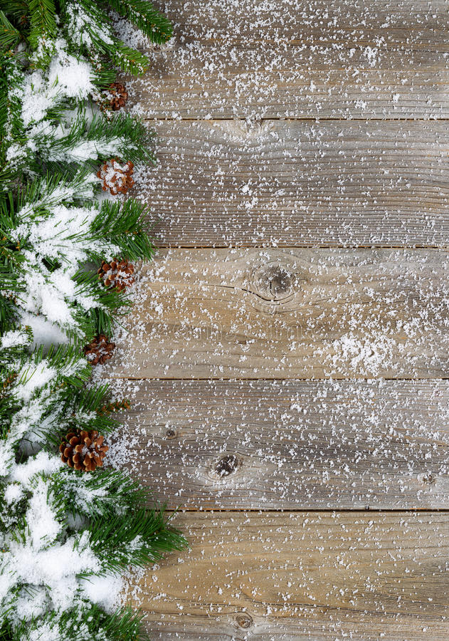 Christmas border with snow covered evergreen branches on rustic. Christmas border with pine tree branches, cones and snow on rustic wooden boards. Layout in stock photo
