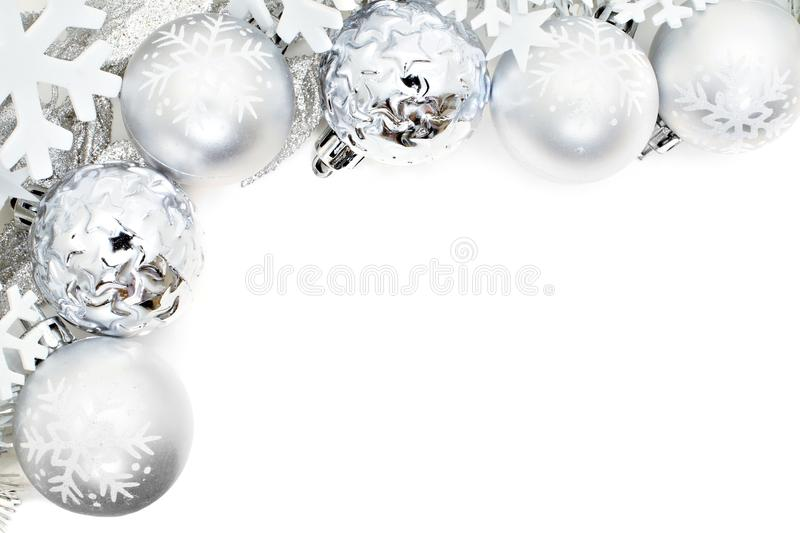 Christmas border of snowflakes and silver baubles. Christmas corner border of snowflakes and silver baubles over a white background royalty free stock photo