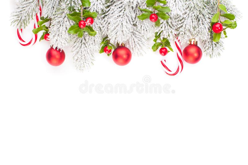 Christmas border. Winter Xmas tree branch, red holly berries and glass balls. New Year decoration isolated on white.  stock photos