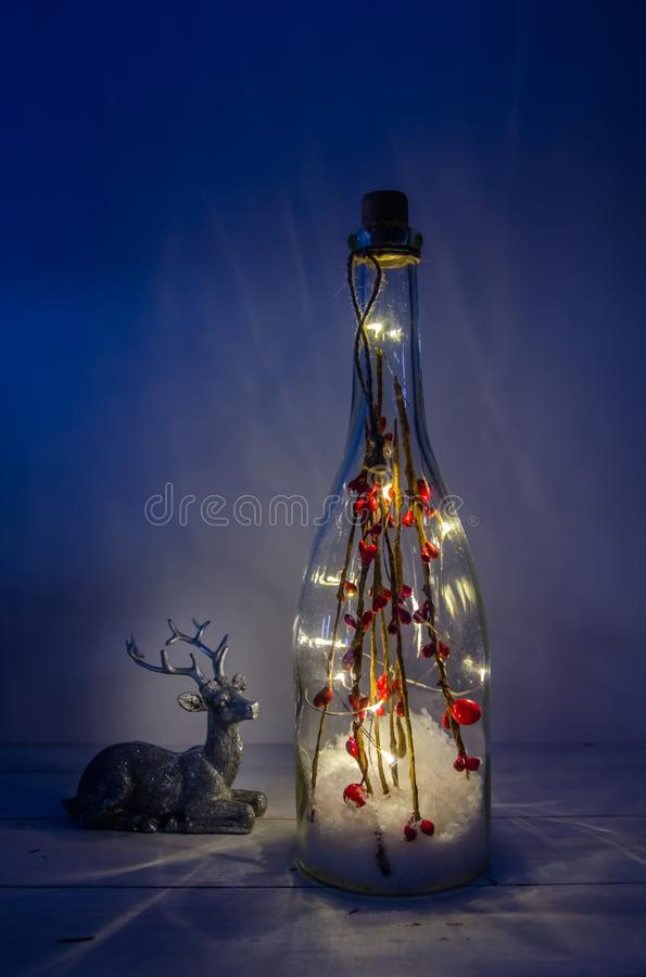 Christmas bottle with lights on a white background. With deer royalty free stock image