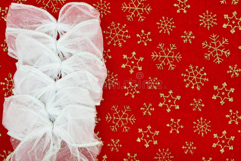 Christmas Bow Border. Silver bows making a border on a red snowflake background, Christmas bow border royalty free stock photos