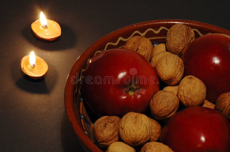 Christmas bowl and candles. Apples and nuts in a bowl with two candles made from nutshells stock photos