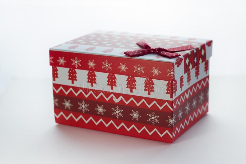 Christmas box with red gifts on white isolated background with the image of Christmas trees close-up angled royalty free stock photo