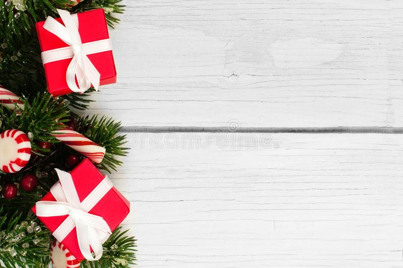 Christmas branches, gifts and candy canes border on white wood. Christmas side border of gifts, branches and candy canes against a white wood background stock photography
