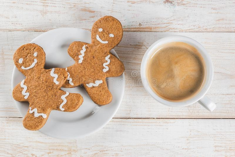 Coffee mug with gingerbread man. Christmas breakfast, coffee mug with gingerbread man cookies, on white wooden table top view copy space royalty free stock photo