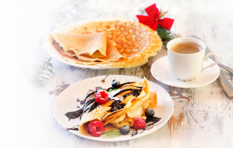 Christmas breakfast. Cup of Coffee and Crepes with fresh berries. Selective focus stock photos