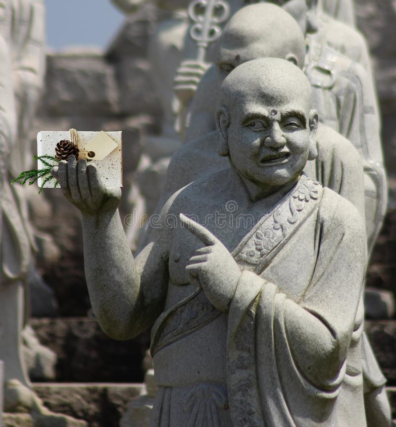 Christmas Buddhist monk statue holding a present with a blank card and pointing at it stock photos
