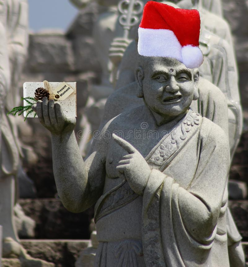 Christmas buddhist monk statue pointing at a gift that says present moment and wearing a santa claus hat. A Christmas buddhist monk statue pointing at a gift stock photography
