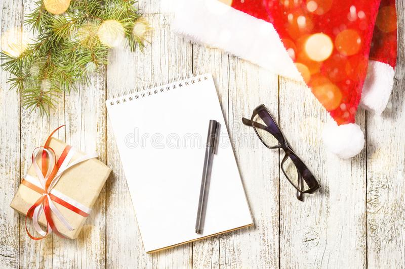 Christmas and Business Items with Copy Space cropped Santa Cap Notepad Pen Glasses and decorated Gift Box and fir tree. Decorated with snow royalty free stock image