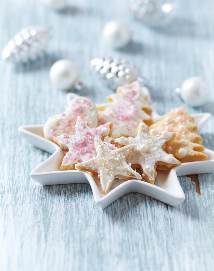 Christmas butter cookies with icing and sugar pearls. Bright wooden background. Close up stock photo