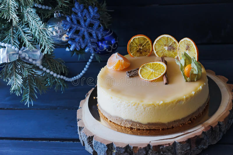 Christmas cake with cinnamon and orange under Christmas tree royalty free stock image