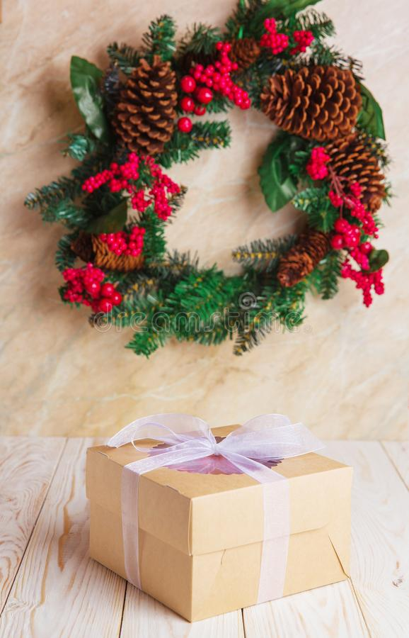 Christmas cake in delivery box with berries. On white wooden background with wreath royalty free stock photo