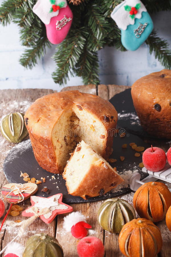 Christmas cake panettone surrounded by holiday decoration close-up. vertical royalty free stock photo