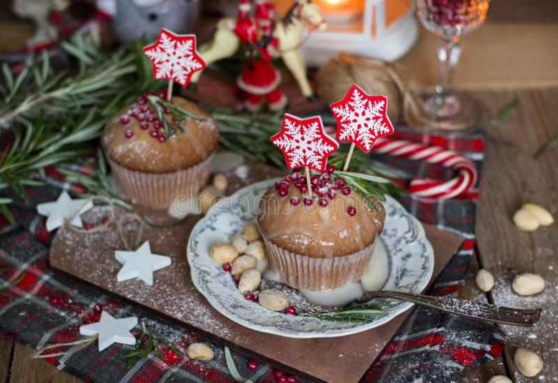 Christmas cake with rosemary and red topping. Decorated with snowflake toppers on wood royalty free stock photo