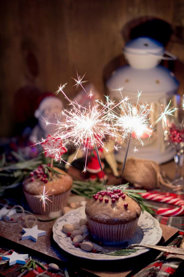 Christmas cake with sparklers and decorations. Christmas cake with sparklers, decorated with rosemary, red topping and snowflake toppers on wood royalty free stock photography