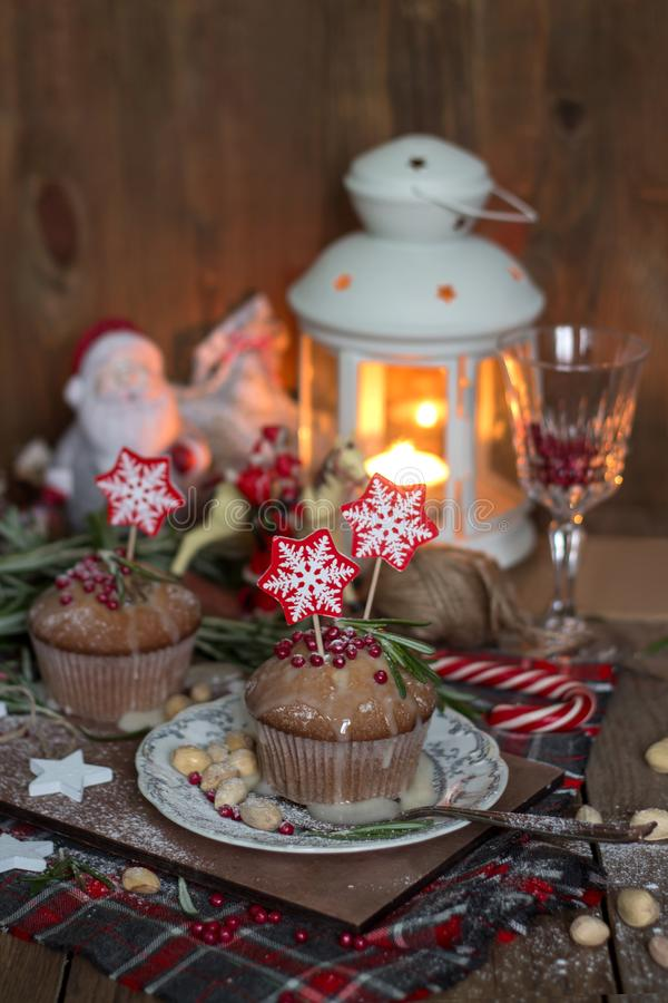 Christmas cake with sparklers and decorations. Christmas cake with sparklers, decorated with rosemary, red topping and snowflake toppers on wood stock photography