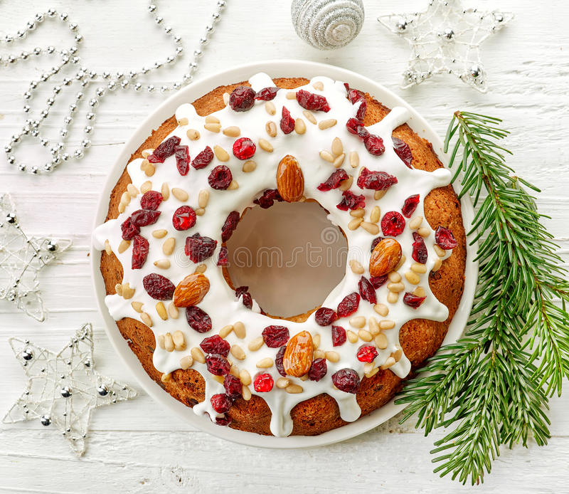 Christmas cake on white wooden table. Christmas cake with fruits and nuts on white wooden table, top view stock photography