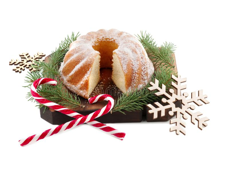 Christmas cake on a wooden board and two Christmas candies. Isolated on white. stock image