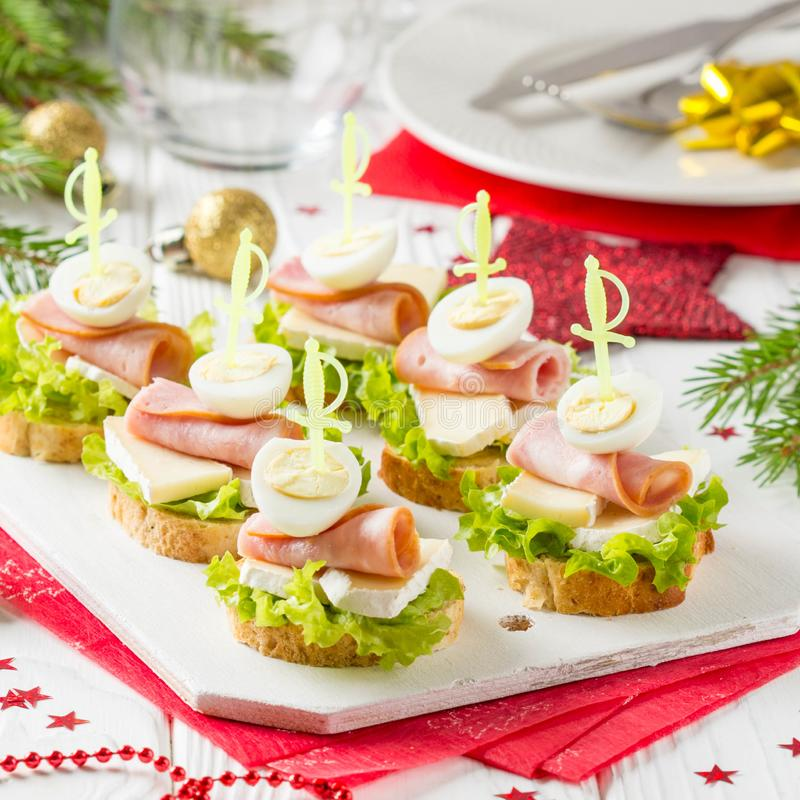 Christmas canapes on bread with brie or Camembert cheese, ham and boiled quail egg. Beautiful presentation on the festive new year royalty free stock image