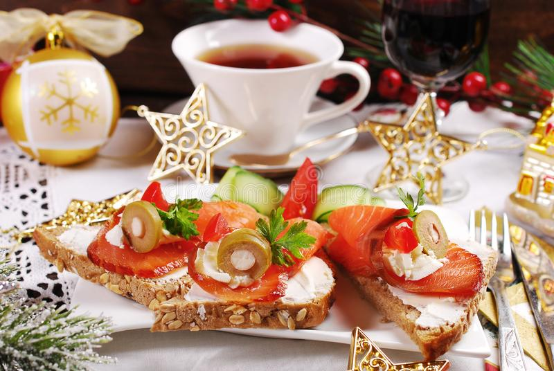 Christmas canapes with salmon and cheese. Christmas canapes with salmon cones filled with cheese and olives on festive table stock photography
