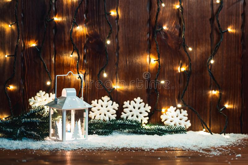 Christmas candle lantern and Christmas tree branches, snow, snowflake and decorations on bokeh background blurred lig royalty free stock photos