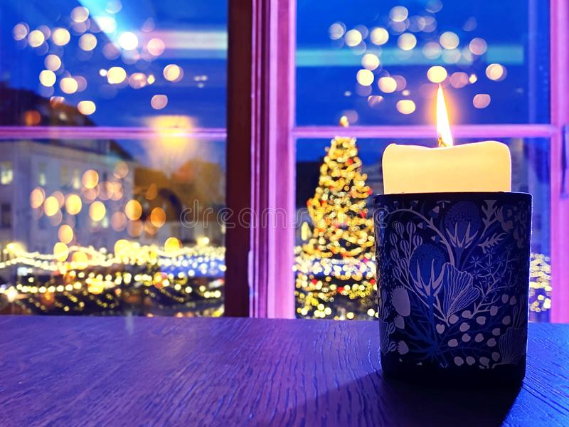 Christmas candle light in blue cup on wooden  window top restaurant interiors  window night city light  reflection blurred ,Tallin stock image