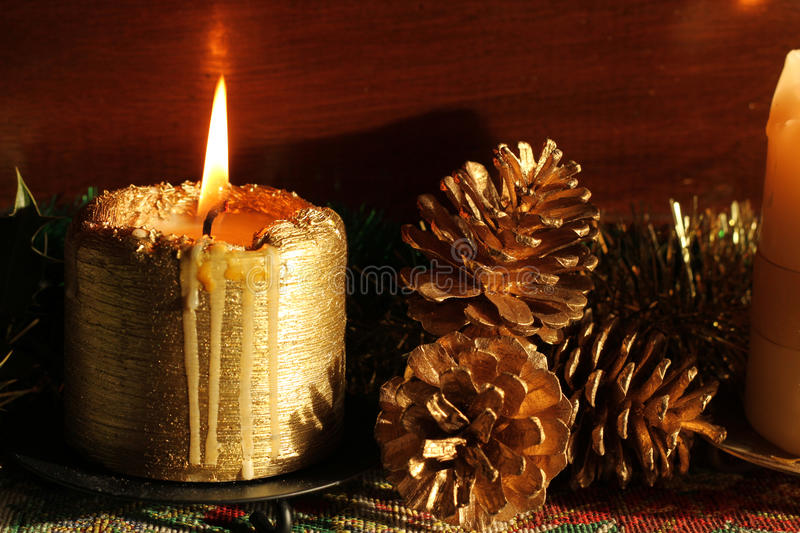Christmas candle and pine cones. Christmas gold candle and decorative pine cones arrangement representative of peace stock images