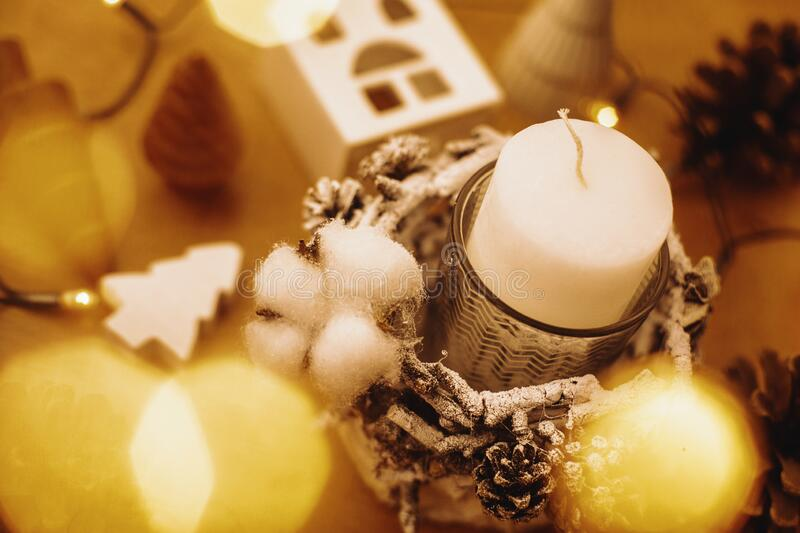 Christmas candle in rustic holder made of branches, cotton, anise and pine cones on wooden table in festive lights bokeh. Rustic stock images