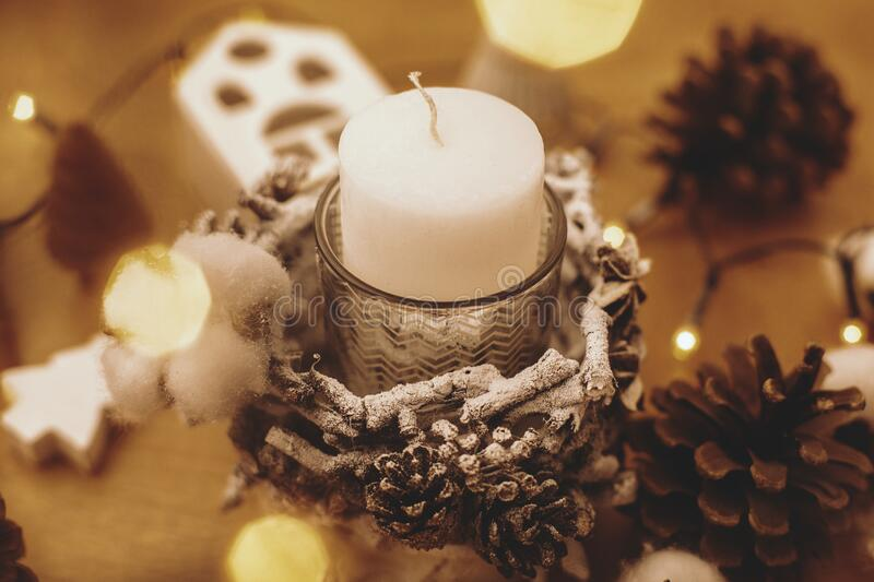 Christmas candle in rustic holder made of branches, cotton, anise and pine cones on wooden table with festive lights. Holiday stock image