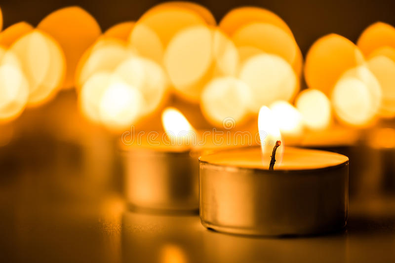 Christmas candles burning at night. Abstract candles background. Golden light of candle flame. stock photos
