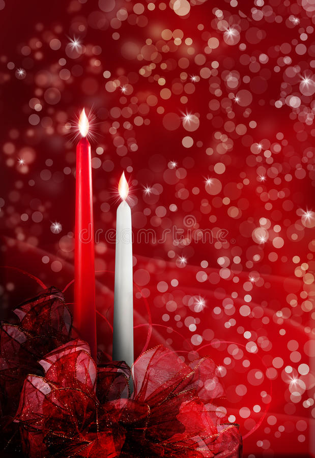 Christmas candles. A red and white candle with flame and red bows at the base. Christmas concept