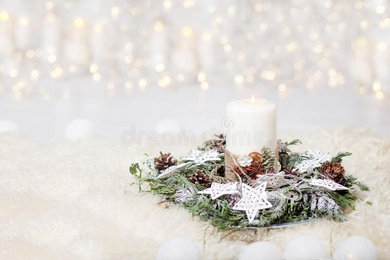 Christmas candles and snowy fir branches over white wooden background with lights.  New Year`s decoration with a fir tree in whit stock photos
