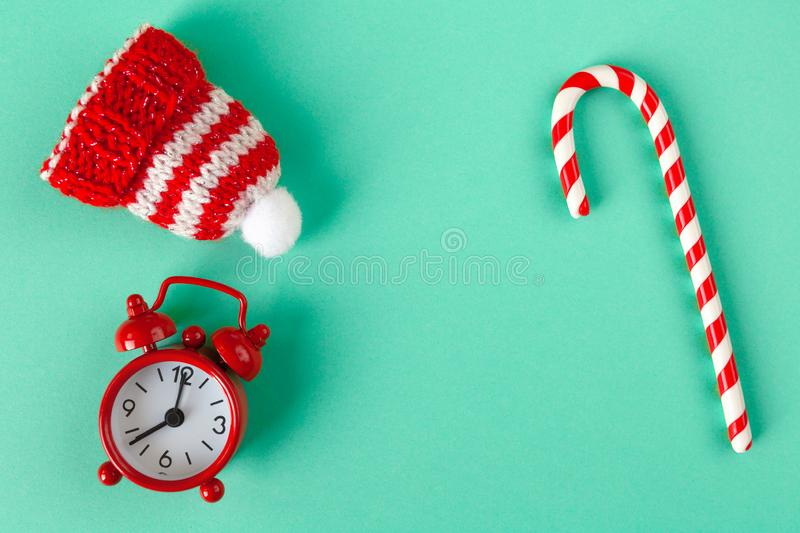 Christmas candy cane, clock and hat on pastel turquoise backdrop with copy space. Winter minimalistic flat lay. Horizontal. Top. View. Still life. Waiting for stock photography