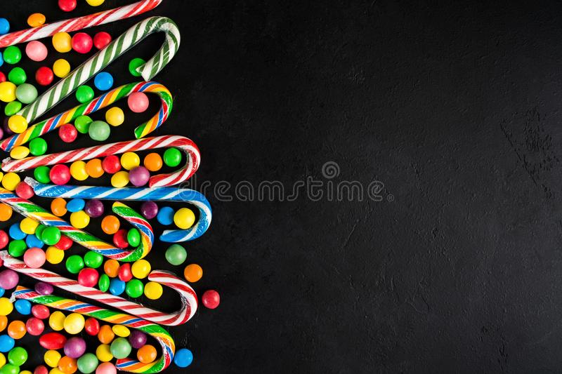 Christmas candy cane with candy drops over black background with stock photography