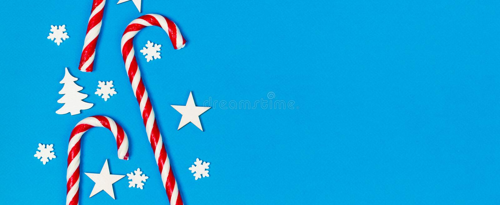 Christmas candy cane lied evenly in row on blue background with decorative snowflake and star. Flat lay and top view royalty free stock images