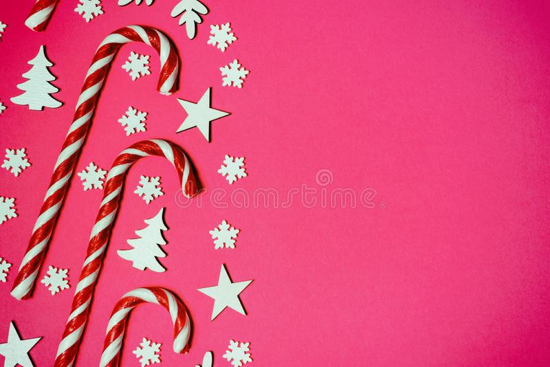 Christmas candy cane lied evenly in row on pink background with decorative snowflake and star. Flat lay and top view stock images