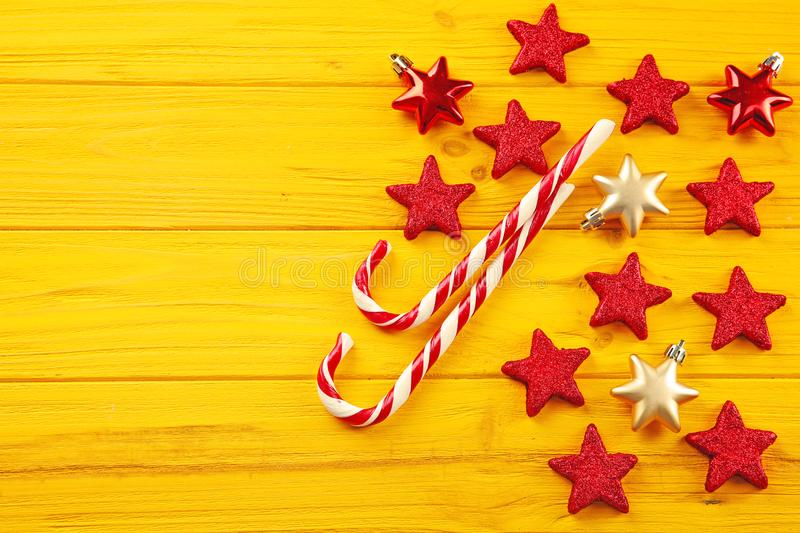 Christmas candy canes and stars on yellow background royalty free stock photography