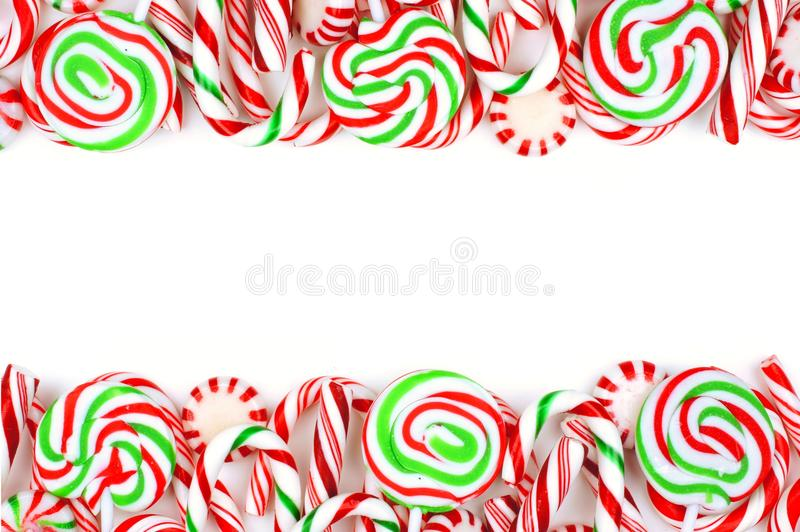 Christmas candy double border over a white background. Christmas candy double border with lollipops, peppermints and candy canes over a white background stock photo