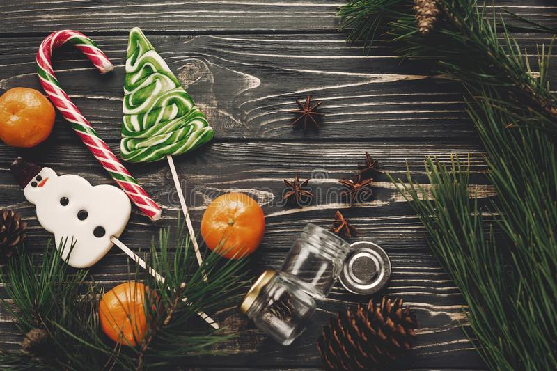 Christmas candy and tangerines with green fir branches with cone royalty free stock image