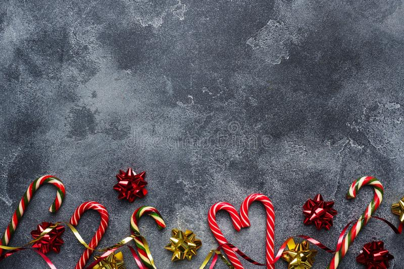 Christmas canes caramel red gold scenery on dark grey background. Copy space Frame stock photo