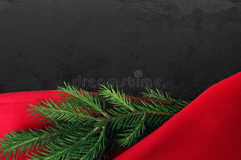 Christmas card background. New year holiday. Christmas still life. Free space for text. Green pine branches on a red and black bac. Kground. Creative composition stock photography